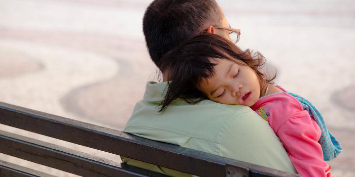 お父さんに抱かれて寝る子ども
